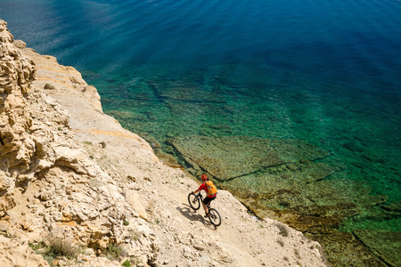 man beach: Mountain biker riding a bike at the seaside and mountains landscape. Man cycling MTB on enduro trail dirt path. Sport fitness motivation and inspiration in beautiful environment. Stock Photo