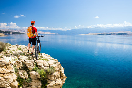 Mountain biking rider with bike looking at inspiring sea and mountains landscape. Man cycling MTB on enduro rocky trail path at sea side. Summer sport, training fitness motivation and inspiration.