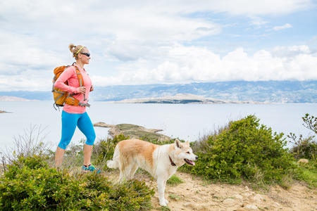 adriatic: Woman hiking with akita inu dog on seaside trail. Recreation and healthy lifestyle outdoors in summer mountains and sea nature. Beautiful inspirational landscape. Trekking and activity concept.