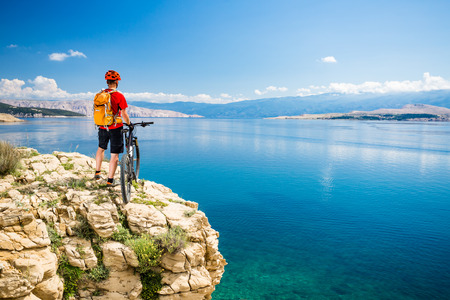 Mountain biker looking at view and traveling on bike in summer sea landscape. Man rider cycling MTB on country road or single track. Fitness motivation, inspiration in beautiful inspirational view.