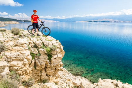 croatia: Mountain biker looking at view and traveling on bike in summer sea landscape. Man rider cycling MTB on country road or single track. Fitness motivation, inspiration in beautiful inspirational view, Croatia.