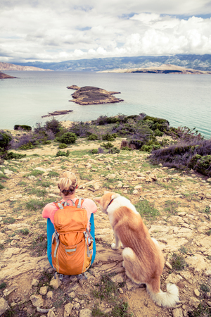 croatia: Woman hiking with akita inu dog on seaside trail. Recreation and healthy lifestyle outdoors in summer mountains and sea nature. Beautiful inspirational landscape. Trekking and activity concept.