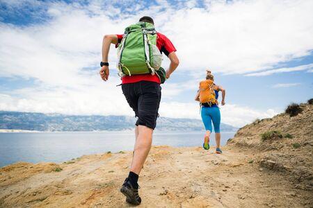 haciendo ejercicio: corredores pareja que lleva con mochilas en la pista de roca a orilla del mar y las montañas. mujer joven y pista de hombre corriendo en la ruta de montaña en busca hermosa vista del paisaje inspirador. Foto de archivo