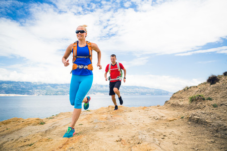 trails: Couple runners running with backpacks on rocky trail at seaside and mountains. Young woman and man trail running on mountain path looking at beautiful inspirational landscape view.
