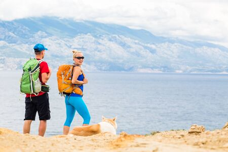 Happy couple hikers trekking with akita dog in summer mountains, camping at seaside. Young woman and man walking on rocky mountain trail path looking at beautiful inspirational landscape view.