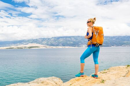croatia: Woman hiker hiking with backpack, looking at sea and mountains view. Recreation and healthy lifestyle outdoors in summer nature. Beautiful inspirational landscape. Trekking and activity concept.
