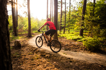 Mountain biker riding on bike in spring inspirational mountains landscape. Man cycling MTB on enduro trail track. Sport fitness motivation and inspiration.