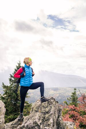 healthy looking: Woman hiking in autumn mountains and woods. Celebrate mountain top, inspiring recreation and healthy lifestyle outdoors in beautiful nature. Motivated backpacker blond female looking at sunset view.