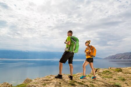 teamwork people: Happy couple hikers trekking in summer mountains on island seaside. Young woman and man walking with backpack on rocky mountain trail. Camping and looking at beautiful inspirational landscape view.