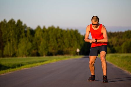 taking pulse: Man runner running on country road in summer sunset. Checking sports watch, ready to run. Young athlete male training and doing workout outdoors in nature.Sport training and fitness concept outdoors. Stock Photo