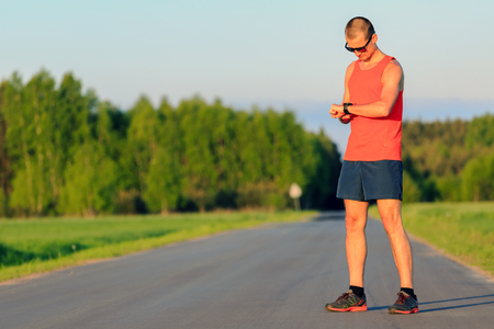 Man runner running on country road in summer sunset. Checking sports watch, ready to run. Young road runner athlete male training and doing workout outdoors in nature.Sport training and fitness concept outdoors. Stock Photo