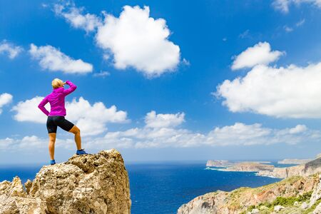 fitness goal: Climber or runner winner reaching life goal success on mountain top. Woman celebrating and looking at inspirational landscape view on rocky peak. Sport and fitness motivation in summer nature.