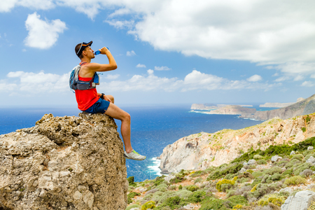trails: Hiker, climber or runner man looking at beautiful ocean and mountains, resting and drinking water from bottle, inspirational landscape view. Fitness, sport motivation outdoor in wild summer nature.