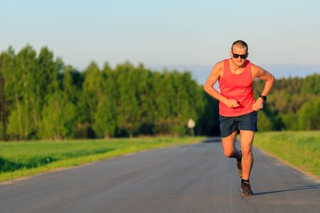 Man runner running on country road, training inspiration and motivation in summer sunset. Young road runner athlete male training and doing workout outdoors in nature, sport and fitness lifestyle.