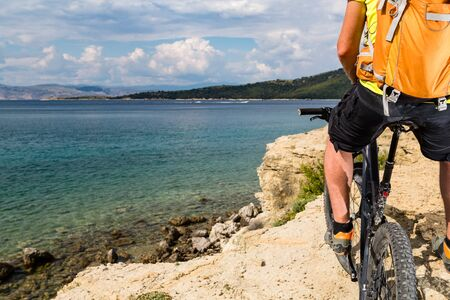 Mountain biker riding on bike at the sea and summer mountains. Man rider cycling MTB on country road or single track. Sport fitness motivation, inspiration in beautiful inspirational landscape view.