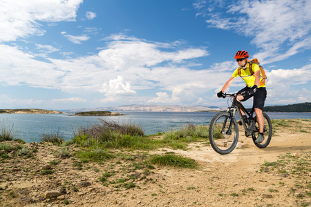 Mountain biker riding on bike at the sea and summer mountains. Man rider cycling MTB on country road or single track. Sport fitness motivation, inspiration in beautiful inspirational landscape. Stock Photo