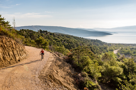 Mountain biker riding on bike in autumn inspirational mountains landscape. Man cycling biking on dirt road, trail track. Sport fitness motivation and inspiration outdoors MTB rider training, Croatia. Stockfoto