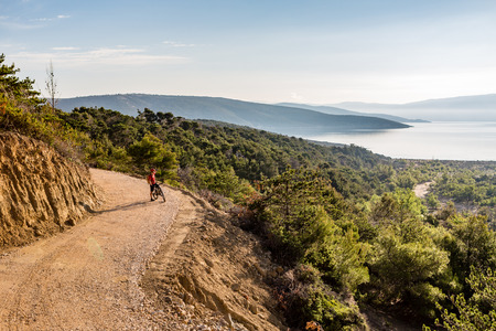 croatia: Mountain biker looking at view, riding on bike in autumn inspirational mountains landscape. Man cycling biking on dirt road. Sport fitness motivation and inspiration MTB rider training, Croatia. Stock Photo