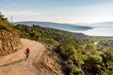 croatia: Mountain biker riding on bike in autumn inspirational mountains landscape. Man cycling biking on dirt road, trail track. Sport fitness motivation and inspiration outdoors MTB rider training, Croatia. Stock Photo