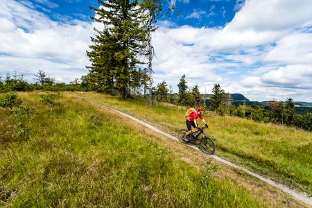 Mountainbiken man rijden op de fiets in de zomer inspirerende bergen landschap. Rider fietsen MTB op enduro trail pad. Sport fitness motivatie en inspiratie. Rider mountainbiker in de zomer bos.