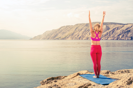 woman stretching: Woman meditating in yoga pose at the sea on rocks. Caucasian blonde girl exercising and training yoga, peaceful stretching with arms outstretched. Fitness and exercising motivation and inspiration.