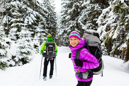 young happy couple: Man and woman happy couple hikers trekking in white winter woods and mountains. Young people walking on snowy trail with backpacks, healthy lifestyle adventure, camping on hiking trip, Poland.