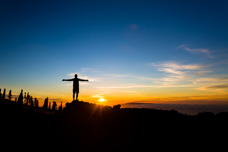Man with arms outstretched celebrating beautiful inspiring sunset in mountains. Male hiker or climber with hands up enjoy inspirational landscape on rocky trail on Tenerife, Canary Islands.