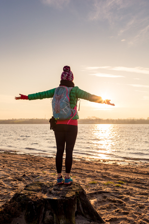 enyoing: Woman hiker with arms outstretched enyoing sunrise and lake, relaxing on beach and sand. Happy female celebrating beautiful morning with backpack looking at inspirational landscape on beach. Stock Photo
