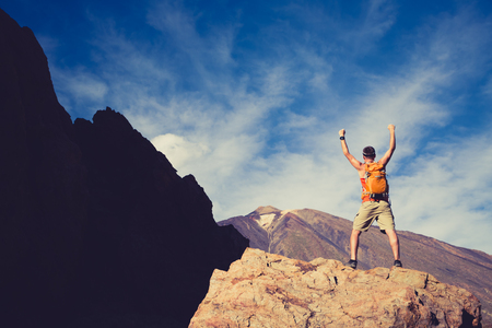 Man with arms outstretched celebrating beautiful inspiring view in mountains. Male hiker or climber with hands up enjoy inspirational landscape on rocky trail on Tenerife, Canary Islands.