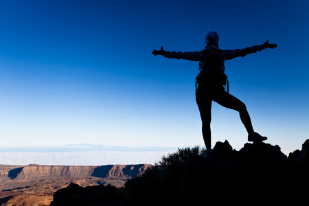 up view: Woman successful hiking climbing silhouette in mountains, motivation and inspiration landscape on island and ocean. Hiker arms up outstretched on mountain top looking at view on Tenerfie, Spain.