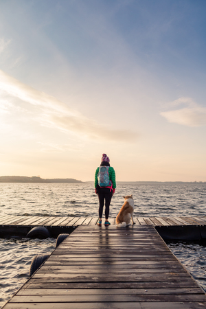 serene landscape: Woman with dog enjoy sunrise and lake, relaxing on bridge. Hiker or tourist looking at beautiful morning view with dog friend, inspirational landscape on beach. Peaceful people and serene concept.