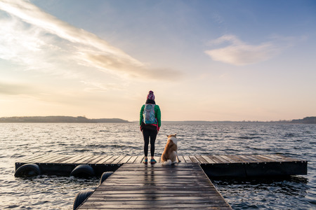 lake sunset: Woman with dog enjoy sunrise and lake, relaxing on bridge. Hiker or tourist looking at beautiful morning view with dog friend, inspirational landscape on beach. Peaceful people and serene concept.