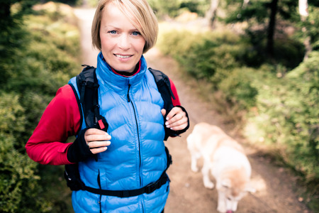 Woman hiking with akita inu dog on forest trail. Recreation and healthy lifestyle outdoors, autumn woods in mountains, inspirational nature. Fitness and trekking and activity concept. Stock Photo