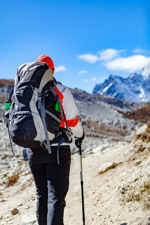 trekking pole: Woman hiker trekking with big backpack in Himalaya Mountains. Person on hiking trail backpacking in high mountains and inspirational landscape. Looking at beautiful mountain view. Stock Photo