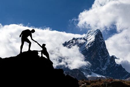 Praca zespołowa turystyka para nawzajem pomagać sylwetkę pomoc ufność w górach, zachód słońca. Zespół wspinaczy mężczyzna i kobieta turystą, pomagając sobie nawzajem na szczycie góry, zaufanie wspinaczka, piękny zachód słońca krajobrazu. Zdjęcie Seryjne