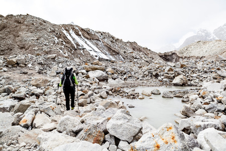 Woman hiker trekking with big backpack in Himalaya Mountains on Rocky Glacier Trail. Girl on hiking trail in high mountains, travel and expedition in inspirational mountain landscape,beautiful views. photo
