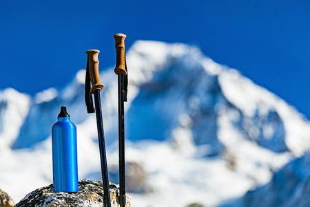 Hiking Gear over Himalaya Mountains Background. Travel Equipment, Trekking Stick and Water Bottle in Inspirational High Himalayas Landscape over Blue Sky in Nepal.