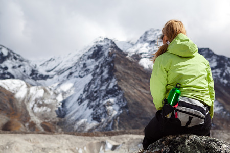 Woman hiker relaxing on rocks in Himalaya Mountains, Nepal. Young Girl Looking at Beautiful Inspirational Landscape. Recreation Meditating Outdoors in High Mountains in Nepal. photo