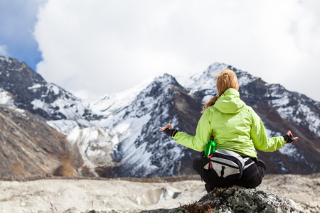 Woman Hiker Meditating on Rocks in Himalaya Mountains, Nepal. Young Girl Looking at Beautiful Inspirational Landscape. Recreation Meditating Outdoors in High Mountains in Nepal. photo