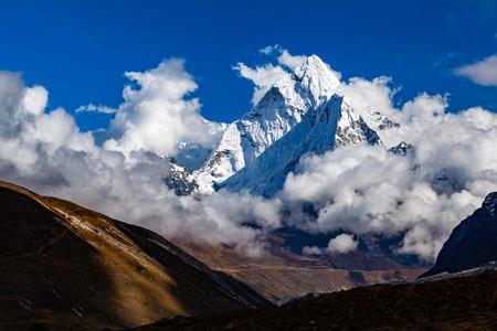 Himalaya Inspirational Landscape, Ama Dablam Mountain in Nepal. Beautiful View on Mountain Peak in Himalayas over Blue Sky.