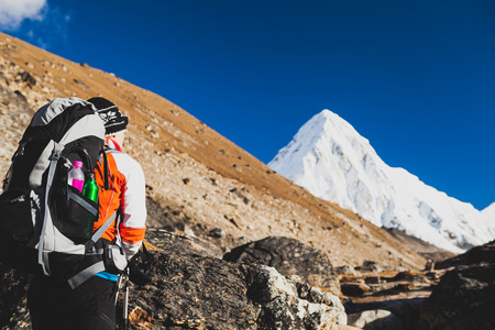 Woman Hiker Hiking in Himalaya Mountains in Nepal. Trekking with backpack in Himalayas to Everest Base Camp. Travel, Exploration and Fitness Concept. Sunny Day with Pumori Summit in Background. photo