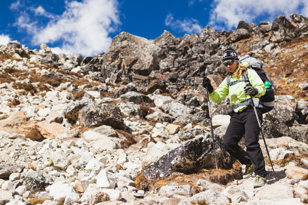 Woman hiker trekking with big backpack in Himalaya Mountains on Rocky Trail. Girl on hiking trail in high mountains, travel and expedition in inspirational mountain landscape with beautiful views. photo