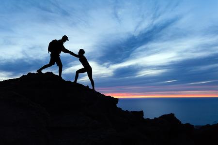 ハイキング、チームワークのカップルは、お互い、信頼案内、山、海に沈む夕日にシルエットを助けます。登山者の人と山の頂上、心に強く訴える