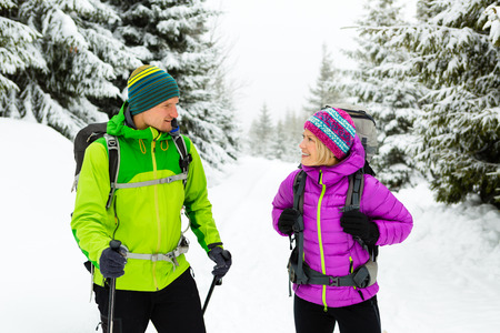 Hombre y mujer pareja feliz excursionistas de trekking en invierno maderas y las montañas. Jóvenes caminando por sendero cubierto de nieve con mochilas, aventura estilo de vida saludable, acampar en viaje de senderismo, Polonia.