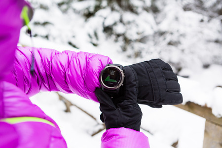 altimeter: Woman hiker checking the elevation on sports watch, smartwatch with altimeter app in winter woods and mountains. Female trekker trekking in white snowy forest with electronics wearable technology.