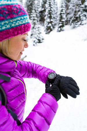 elevation: Woman hiker checking the elevation on sports watch, smartwatch with altimeter app in winter woods and mountains. Girl trekker in white snowy forest trekking with electronics equipment technology.
