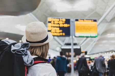 Frau Wanderer mit Rucksack in Flughafen Blick auf die Fluginformationen einen internationalen Flug Überprüfung Ziel zu reisen.