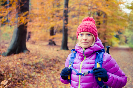 healthy looking: Hiking woman with backpack looking at camera in inspirational autumn golden woods. Fitness travel and healthy lifestyle outdoors in fall season nature. Female backpacker tourist walking in forest.