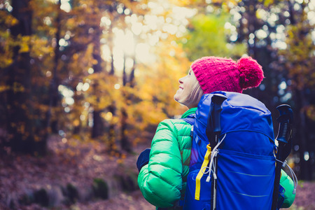 healthy looking: Hiking woman with backpack looking at inspirational autumn golden woods. Fitness travel and healthy lifestyle outdoors in fall season nature. Female backpacker tourist walking and looking around.