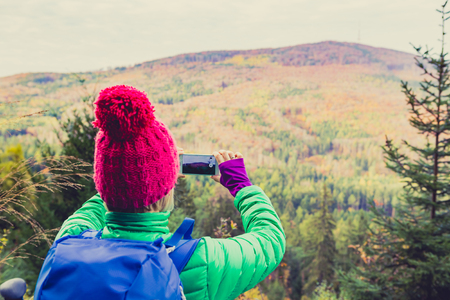 healthy looking: Hiking woman with backpack looking at inspirational autumn woods, taking photo with smartphone. Travel and healthy lifestyle outdoors in fall season.Female backpacker tourist photographing landscape.